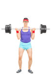 Determined guy lifting a heavy barbell Stock Photo