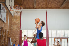 Determined high school kids playing basketball royalty free stock photography