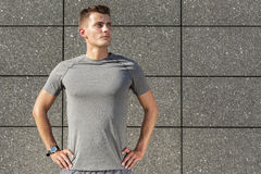 Determined jogger standing against tiled wall outdoors Royalty Free Stock Images