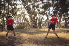 Determined kids practicing tug of war during obstacle course stock images