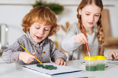Determined little artist painting a tree. Many shades. Enthusiastic creative cute boy using green watercolors and a big brush creating green variety on his paper royalty free stock image