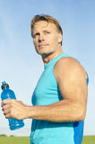 Determined looking sportsman. Determined looking sportsman wearing a blue tank top and holding a blue water water bottle Royalty Free Stock Photos