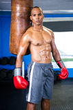 Determined male boxer standing by punching bag Royalty Free Stock Photo