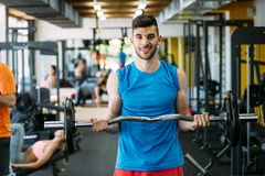 Determined male exercising in gym. Keeping body in shape stock photos