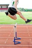 Determined male idrottsman nen som hoppar den ovannämnda häcken royaltyfria foton