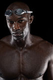 Determined male swimmer with goggles. Determined swimmer with wet body looking at camera. Portrait of young afro american male athlete with muscular body against Royalty Free Stock Photo