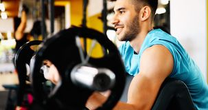 Determined male working out in gym. Lifting weights Stock Photos