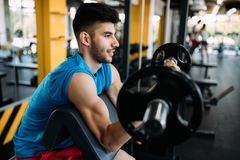 Determined male working out in gym. Lifting weights Royalty Free Stock Photo