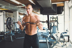 Determined male working out in gym. Lifting weights Royalty Free Stock Photos