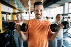 Determined male working out in gym. Lifting weights Stock Photography