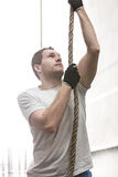 Determined man climbing rope in crossfit gym Stock Photos