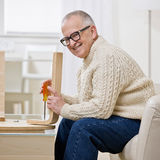Determined man constructing wooden table. Using screwdriver stock photos
