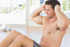 Determined man doing abdominal crunches at gym Stock Photography