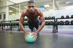 Determined man doing push ups with ball in gym Royalty Free Stock Images