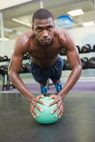 Determined man doing push ups with ball in gym Royalty Free Stock Image