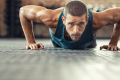 Determined man doing push ups at the gym. Young athlete doing push ups as part of bodybuilding training. Muscular guy doing a pushup on floor at crossfit gym royalty free stock photo