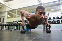 Determined man doing push ups with kettle bells in gym Stock Image
