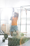 Determined man hitting tire with sledgehammer in crossfit gym Stock Image