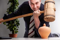 Determined man holding a large wooden mallet. Focused businessman holding a large wooden mallet poised above a pottery urn or money box with a look of fierce stock photo
