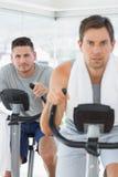 Determined man using exercise bike Royalty Free Stock Photo