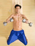 Determined man working out with dumbbells. Determined bare chested man working out with dumbbells in health club Royalty Free Stock Photography