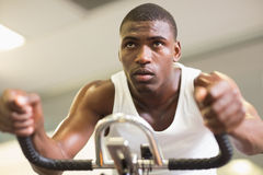 Determined man working out on exercise bike at gym Royalty Free Stock Photo