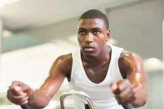 Determined man working out on exercise bike at gym Royalty Free Stock Photos
