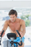Determined man working out at spinning class in bright gym Royalty Free Stock Images