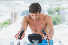 Determined man working out at spinning class in bright gym Stock Image