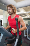 Determined man working out on x-trainer in gym Royalty Free Stock Photo