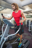 Determined man working out on x-trainer in gym Royalty Free Stock Photos