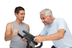 Determined mature man on stationary bike with trainer Stock Images