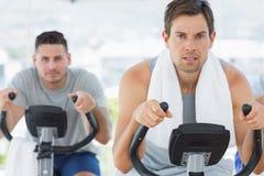 Determined men using exercise bikes Stock Photo