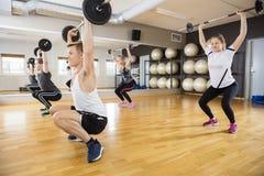 Determined Men And Women Lifting Dumbbells On Hardwood Floor Stock Image