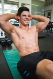 Determined muscular man doing abdominal crunches Royalty Free Stock Images