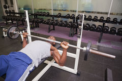 Determined muscular man lifting barbell in gym Stock Photography