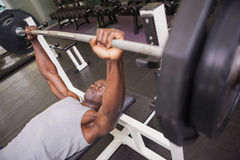 Determined muscular man lifting barbell in gym Royalty Free Stock Photo