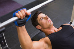 Determined muscular man lifting barbell in gym Stock Images