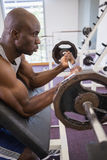 Determined muscular man lifting barbell in gym Stock Photos