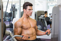 Determined muscular man working on abdominal machine Stock Photography