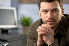 Determined office worker. Sitting at desk, thinking Royalty Free Stock Photo