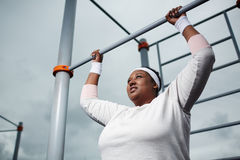 Determined overweight African woman practicing pull-up exercise outdoors. Pull-up challenge for overweight woman stock image