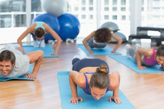 Determined people doing push ups in fitness studio Stock Images