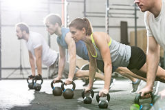 Determined people doing pushups with kettlebells at crossfit gym stock photos