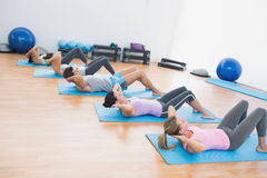 Determined people doing sit ups in fitness studio Royalty Free Stock Image