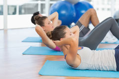 Determined people doing sit ups in fitness studio Stock Images