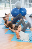 Determined people doing sit ups in fitness studio Stock Image