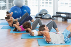 Determined people doing sit ups in fitness studio Stock Photos