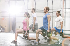 Determined people lifting kettlebells at crossfit gym royalty free stock image