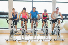 Determined people working out at spinning class in gym Stock Images